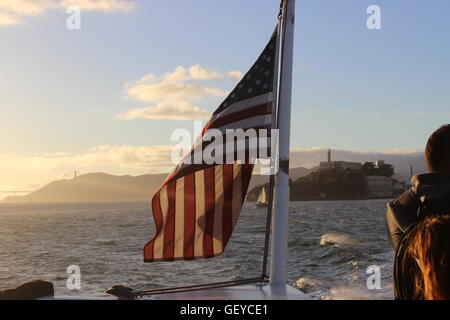 A photograph of the American Flag in beautiful sunlight/sunset on the San Francisco to Sausalito Cruise - Stock Photo