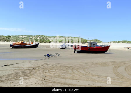 Barmouth, Wales, UK. July 19, 2016.  Beached boats at low tide with the beach and sand dunes. - Stock Photo