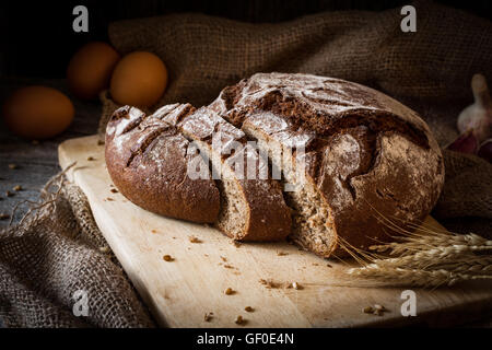 Sourdough rye bread sliced on wooden cutting board. Rustic still life. Natural light, low key - Stock Photo