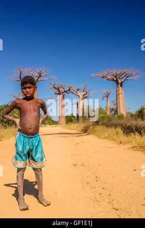 Young malagasy boy standing on the sandy road in the Avenida de baobab near Morondava in Madagascar. Picture taken - Stock Photo
