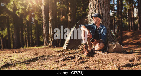 Portrait of senior man sitting by a tree with a tent in background. Mature man sitting at a campsite. - Stock Photo