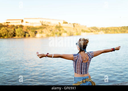 Woman freely spreads arms and enjoys river flow - Stock Photo
