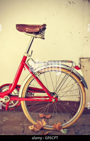 Retro bicycle with autumn leaves on the rear wheel. Vintage style. Vertical image - Stock Photo