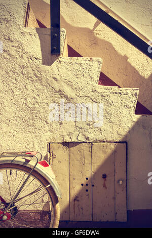 Detail of retro bicycle wheel. It looks part of the rear fender, brake and an old staircase. Vintage style. Vertical - Stock Photo