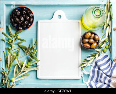Two bowls with pickled green and black olives, olive tree sprigs, oil in glass bottle, white ceramic board in center. - Stock Photo
