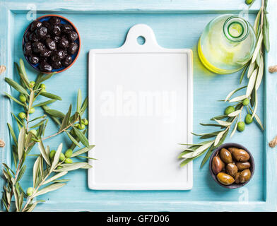 Two bowls with pickled green and black olives, olive tree sprigs, oil, white ceramic board in center. Copy space. - Stock Photo