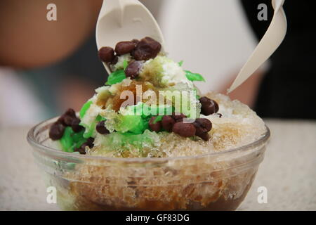 Ice Kacang (shaved ice with red bean) being mixed ready to be consumed. - Stock Photo