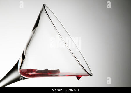 Oblique view of an empty martini glass with red drops on the edge of the glass - Stock Photo