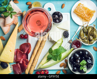 Summer wine snack set. Glass of rose, meat, cheese, olives, honey, bread sticks, nuts, capers and berries with white - Stock Photo