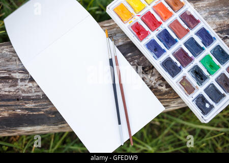 Mock up with blank paper notebook and watercolor set with brushes lying on the old wood. Top view image - Stock Photo