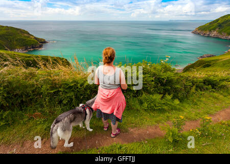A woman dog walking along the coastal path around Lantic Bay, Cornwall, UK with the camera in shot on a summers - Stock Photo