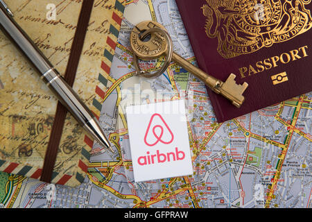 An Airbnb branded key fob with a British passport, travel journal, pen and city street map (Editorial use only). - Stock Photo