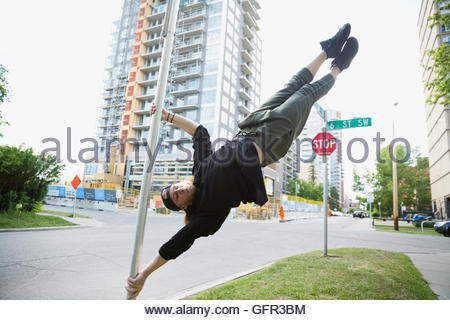 Young man doing parkour on pole in urban street - Stock Photo