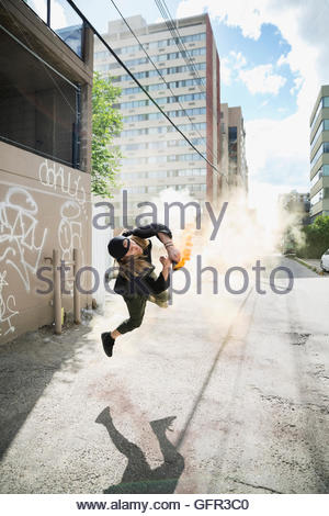 Cool young man doing parkour backflipping with powder cannon in urban alley - Stock Photo