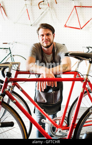 A man working in a bicycle repair shop - Stock Photo