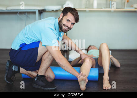 Physiotherapist doing leg therapy to a woman using foam roll - Stock Photo