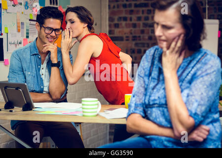 Businesswoman in deep thought and colleagues whispering in background - Stock Photo