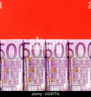 500 euro row on red background in a form of rolls - Stock Photo