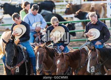 Cowboys & cowgirls with hats removed during prayer; Chaffee County Fair & Rodeo, Salida, Colorado, USA - Stock Photo