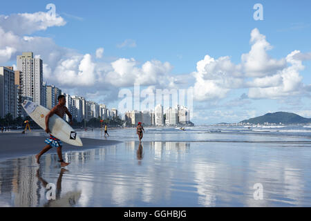 Surfer on the beach in front of apartment buildings, Praia das Asturias, city beach, in Guaruja, Costa Verde, Sao - Stock Photo