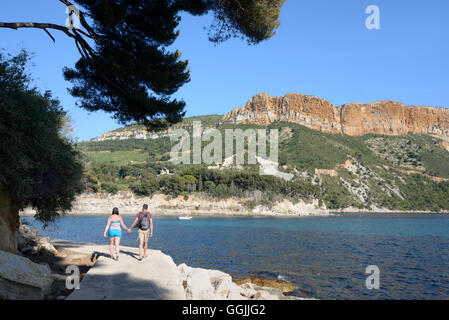 Young Couple of Tourists Walking Hand- in-Hand Along a Coast Path with Cap Canaille & Cliffs in Background Cassis - Stock Photo