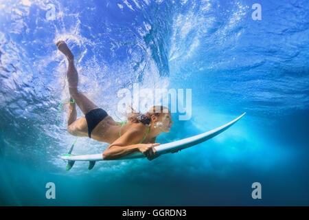 Young active girl in bikini in action - surfer with surf board dive underwater under breaking big ocean wave. school - Stock Photo