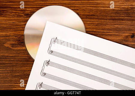 Music sheet and CD drive on wooden background. Old and new technology in music. - Stock Photo