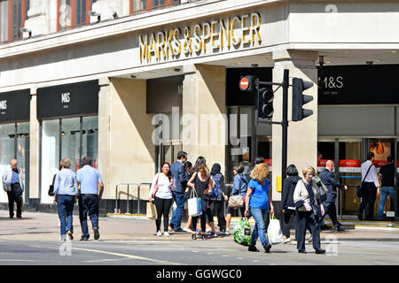 West End shoppers in Oxford Street outside entrance to Marks and Spencer flagship shopping department store in London - Stock Photo