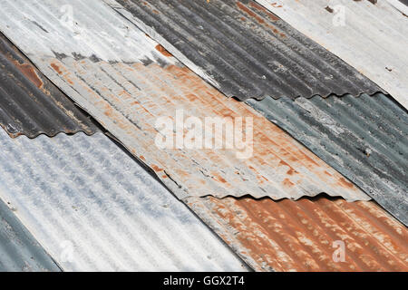 Old weathered corrugated metal as colorful roofing - Stock Photo