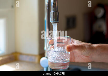 Woman filling a glass of water from a stainless steel or chrome tap or faucet, close up on her hand and the glass - Stock Photo