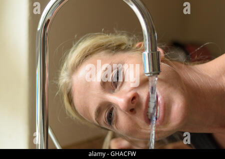 Smiling blond woman drinking water directly from a kitchen faucet bending down letting the running water pour through - Stock Photo