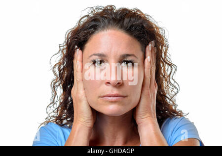 Serious young woman blocking her ears with her hands to avoid hearing something - hear no evil concept isolated - Stock Photo