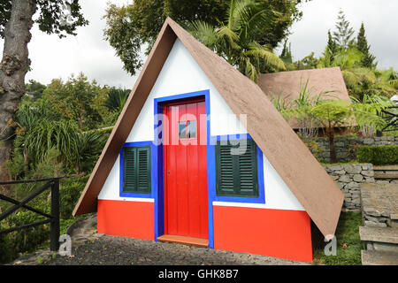 Small rural red, white and blue house with a triangular thatched roof on the island of Madeira, Portugal - Stock Photo
