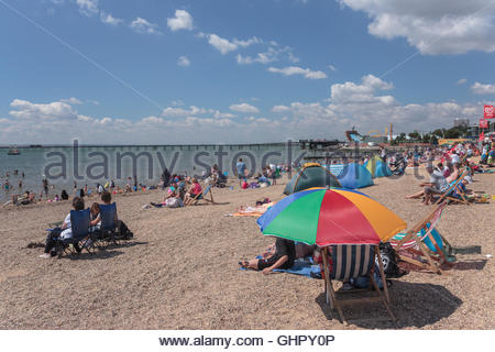 Tourists are sitting on Jubilee beach in Southend-On-Sea, Essex. They are protected from the sun by a parasol. - Stock Photo