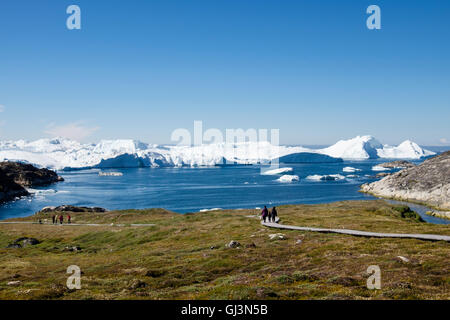 People on a boardwalk across the Sermermiut Inuit settlement archaeological site with icebergs in Disko Bay in summer. - Stock Photo