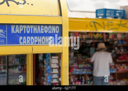 Greek card phone with kiosk in the background, Athen, Greece - Stock Photo