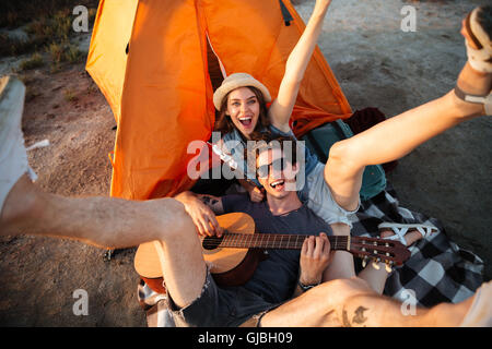 Happy young cheerful couple having fun camping by a lake - Stock Photo