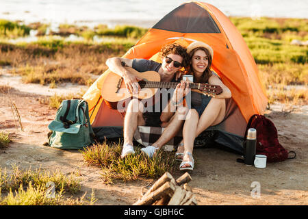 Portrait of a man playing guitar for his girlfriend sitting at the camping tent - Stock Photo