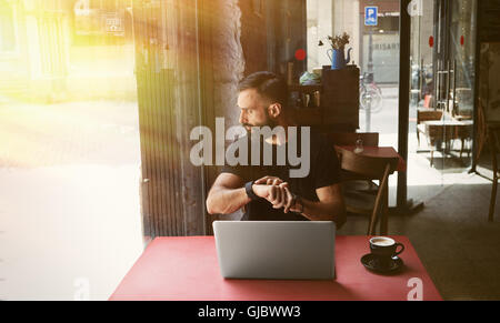 Young Bearded Businessman Wearing Black Tshirt Working Laptop Urban Cafe.Man Sitting Wood Table Cup Coffee Looking - Stock Photo