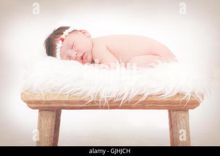 Portrait of a newborn baby girl sleeping on fluffy rug - Stock Photo