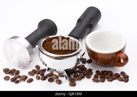 cup,ground coffee in the filter holder of an espresso machine and rammers - Stock Photo
