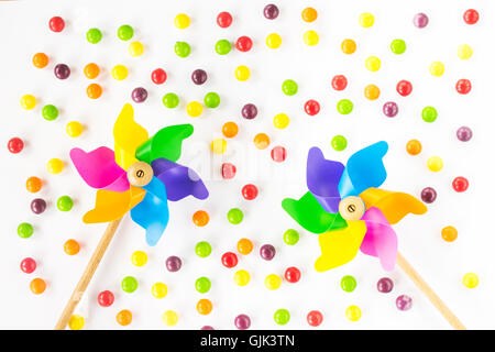 Colorful pinwheels and candies on white background. Top view. Flat lay - Stock Photo
