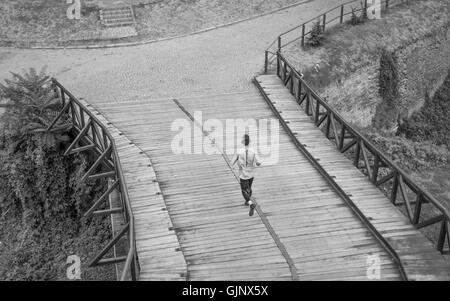 black and white one man run jogging elevated view rear back - Stock Photo