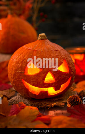 Burning Jack O'Lantern on a rustic table with autumn decorations, darkly lit. - Stock Photo