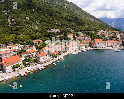 Perast town lies beneath the hill of St. Ilija. Aerial view of shore. Adriatic sea. Kotor bay (Boka Kotorska), Montenegro - Stock Photo