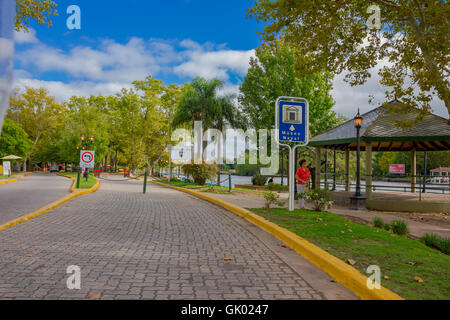 TIGRE, ARGENTINA - MAY 02, 2016: unidentified women walking on the sidewalk next to a nice street close to the river - Stock Photo
