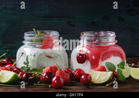 Two Square glass jars with homemade yogurt with mint, strawberry puree, cherry and chia seeds served with fresh - Stock Photo