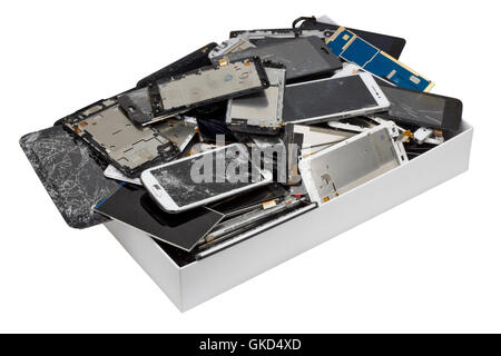 Heap of the  broken  cellular telephons in the white cardboard box. Mass production devices are prepared for industrial - Stock Photo
