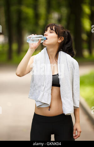 Attractive brunette sporty woman drinking water after fitness in park - Stock Photo