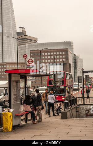 A view of the busy commuter traffic and people crossing London bridge with the Shard in the background - Stock Photo
